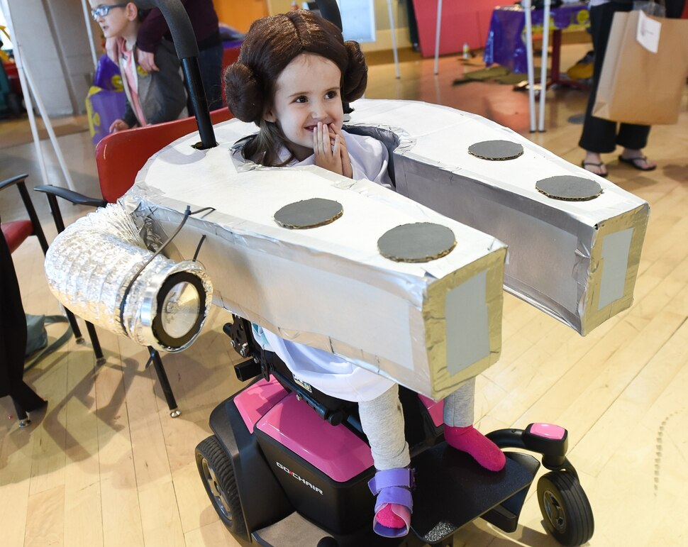 (Francisco Kjolseth | The Salt Lake Tribune) Annika Ellefsen, 4, is all smiles as Princess Leia in her Millennium Falcon as volunteers and staff at Shriners Hospital for Children in Salt Lake transform the wheelchairs of 28 patients for Halloween, Wednesday, Oct. 17, 2018. Annika, who has spina bifida, loves her visits to Shriner's, according to her mother, Jennifer. Last year her wheelchair was transformed into a princess carriage and she beamed all night long, exclaimed her mother.