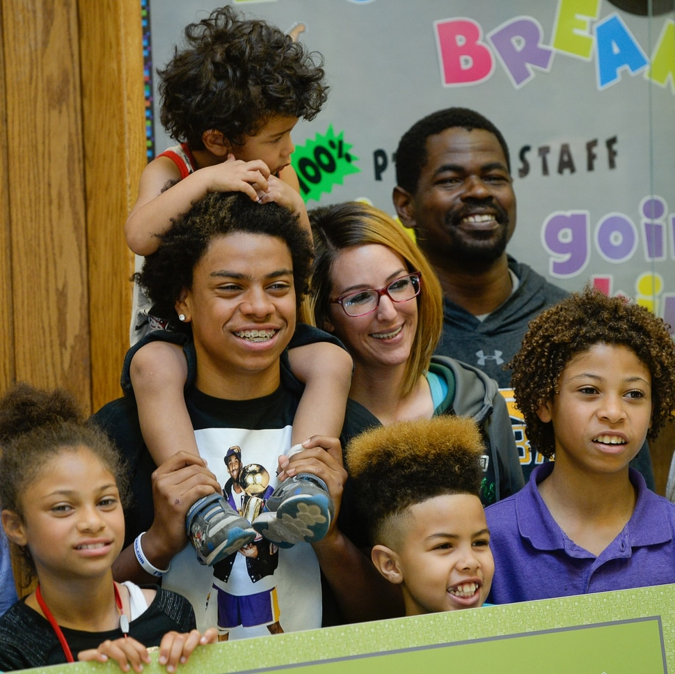 (Francisco Kjolseth | The Salt Lake Tribune) Kearns High sophomore Keeven Wilson, 16, center left, celebrates with his blended family after being announced as the Granite School District's Absolutely Incredible Kid award winner during the school farewell assembly on Tuesday, May 22, 2018. Surrounded by his siblings Kingston, 2, foster parents Jessica and Marcus Wilson, Tyrese, 11, Kamani, 9, and Mya, 8, clockwise from top, Keenen is all smiles as he talked about maintaining his honor roll status and possibly studying psychology in college.