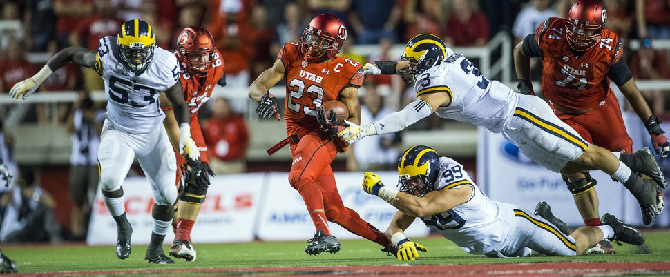 Chris Detrick | The Salt Lake Tribune Utah Utes running back Devontae Booker (23) runs past Michigan Wolverines linebacker Desmond Morgan (3) and Michigan Wolverines defensive tackle Matthew Godin (99) during the second half of the game at Rice-Eccles Stadium Thursday September 3, 2015. Utah defeated Michigan 24-17.