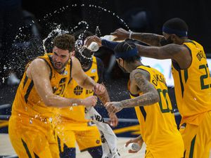 (Rick Egan | The Salt Lake Tribune) Utah Jazz guard Mike Conley (10) Utah Jazz forward Royce O'Neale (23), and Utah Jazz guard Jordan Clarkson (00) spray water on Utah Jazz forward Georges Niang (31),  during his post game interview, in NBA action between the Utah Jazz and the Charlotte Hornets at Vivint Arena, on Monday, Feb. 22, 2021.