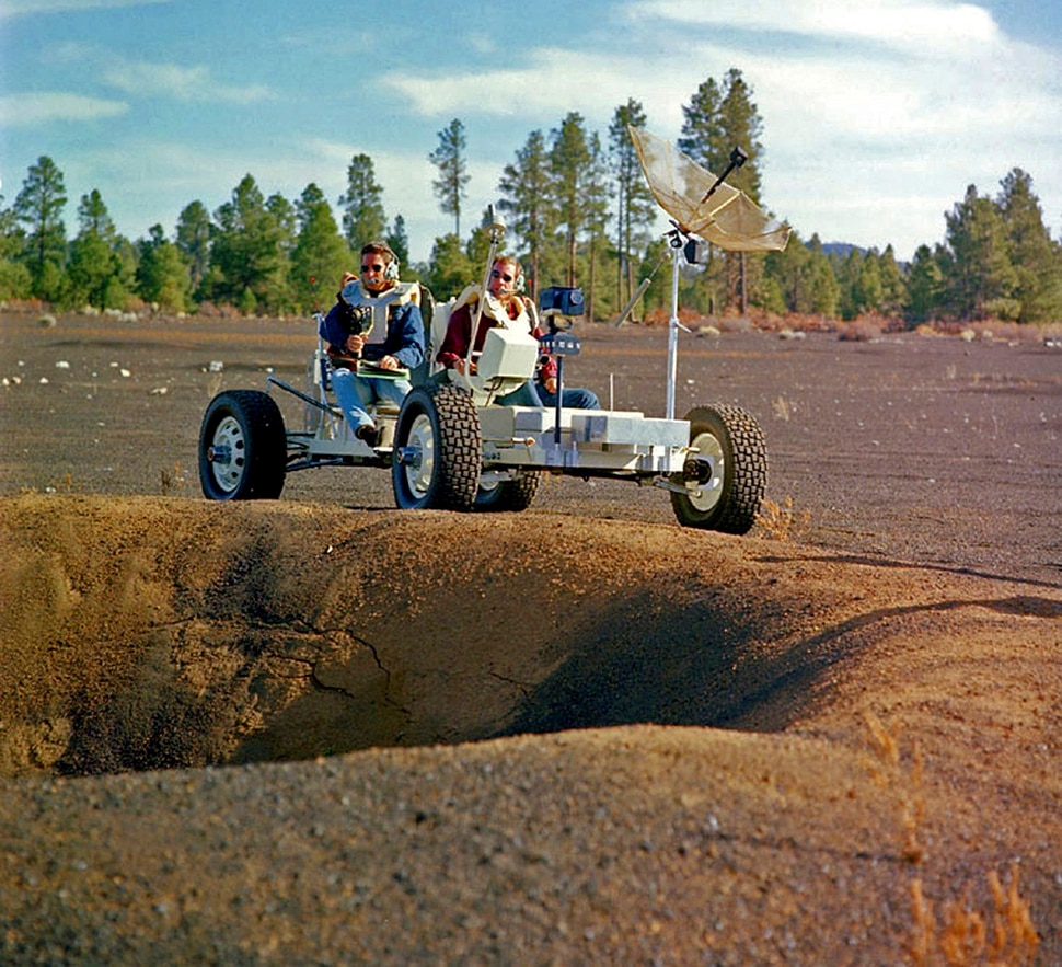 (U.S. Geological Survey Astrogeology Science Center via AP) This undated photo provided by the U.S. Geological Survey Astrogeology Science Center shows Apollo 15 astronauts Jim Irwin, left, and Dave Scott driving a prototype of a lunar rover in a volcanic cinder field east of Flagstaff, Ariz. The rover, named Grover, now is on display at the science center.