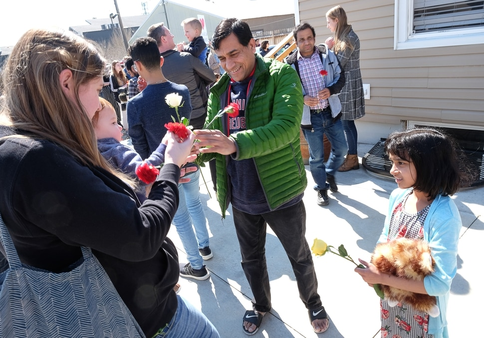 (Francisco Kjolseth | The Salt Lake Tribune) Muhahed Shaikh is joined by his daughter Maryam, 8, as they receive flowers from the community following Friday prayers services at the Al Sahaba Mosque in Orem in a show of love and support following the tragic shootings in New Zealand.