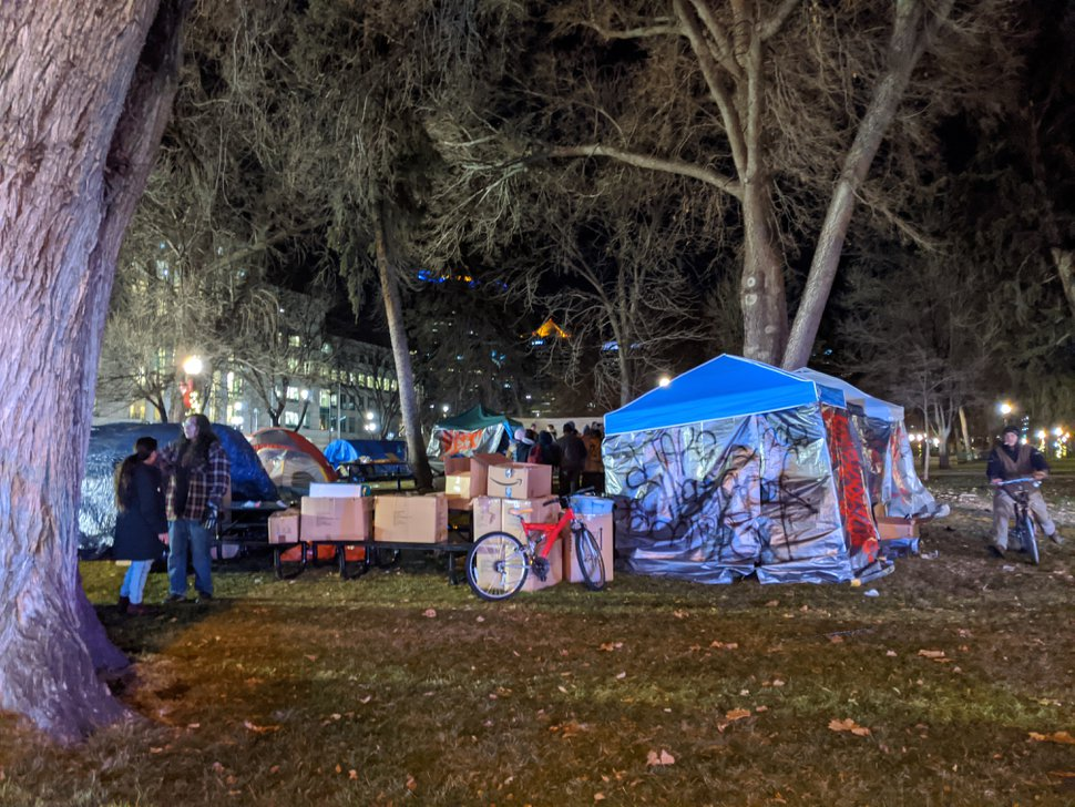 (Paighten Harkins | The Salt Lake Tribune) People stand near tents at a protest at Washington Square Park on Saturday, Jan. 4, 2020. Police later moved in to disperse the demonstrators who were occupying the park. Sixteen people were arrested.