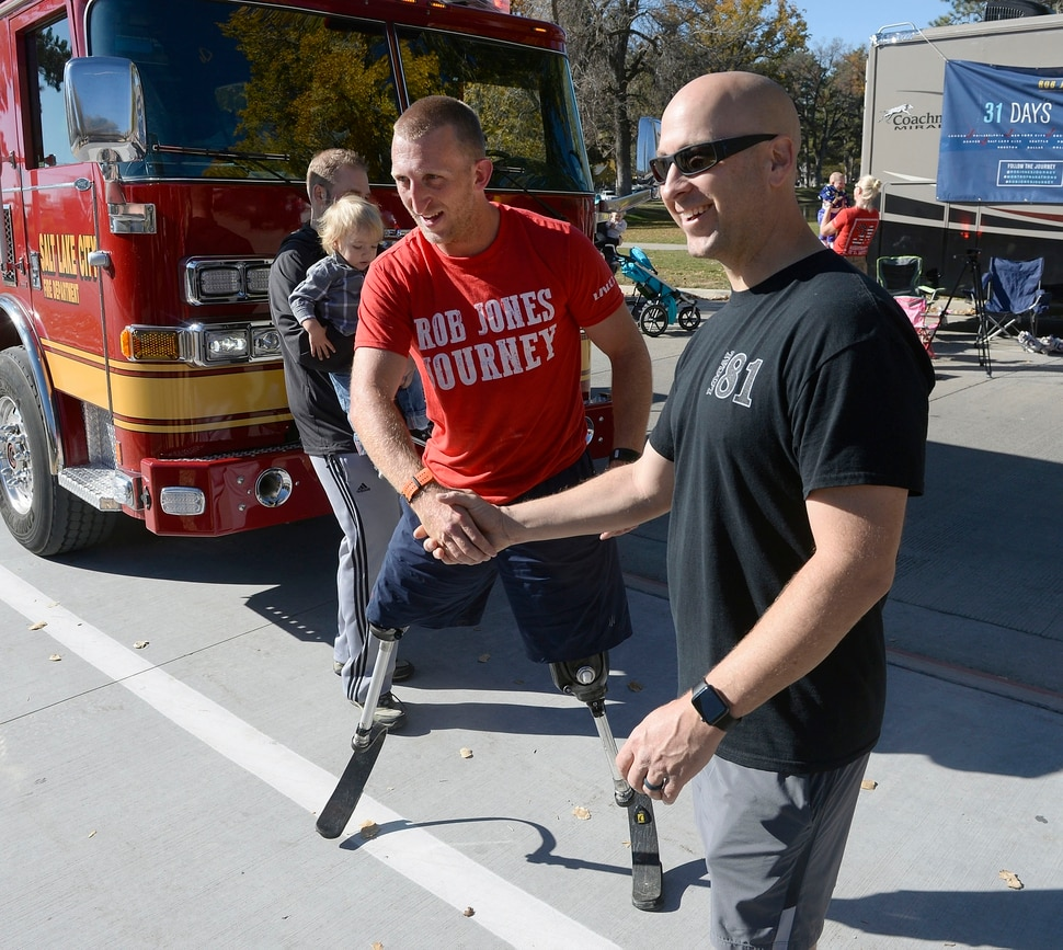 "Al Hartmann | The Salt Lake Tribune) Rob Jones, a retired Marine Corps Sergeant who lost both legs when he stepped on an improvised explosive device in Afghanistan, gets encouragment from Salt Lake City Firemen as he runs a marathon, (26.2) miles in Liberty Park in Salt Lake City Wednesday Oct. 25. He won a Bronze Medal in the Paralympics and he wis the first and only double above the knee amputee to ride a normal bicycle 5,180 miles across America. Now, he is set to run 31 marathons in 31 days in 31 major cities. Starting in London on October 12th, and continuing in the United States and Toronto, he will run 26.2 miles in the selected city on his own, travel to the next city, and repeat, ending appropriately on Veterans Day in our Nation's Capital. His motto, ""Survive. Recover. Live."""