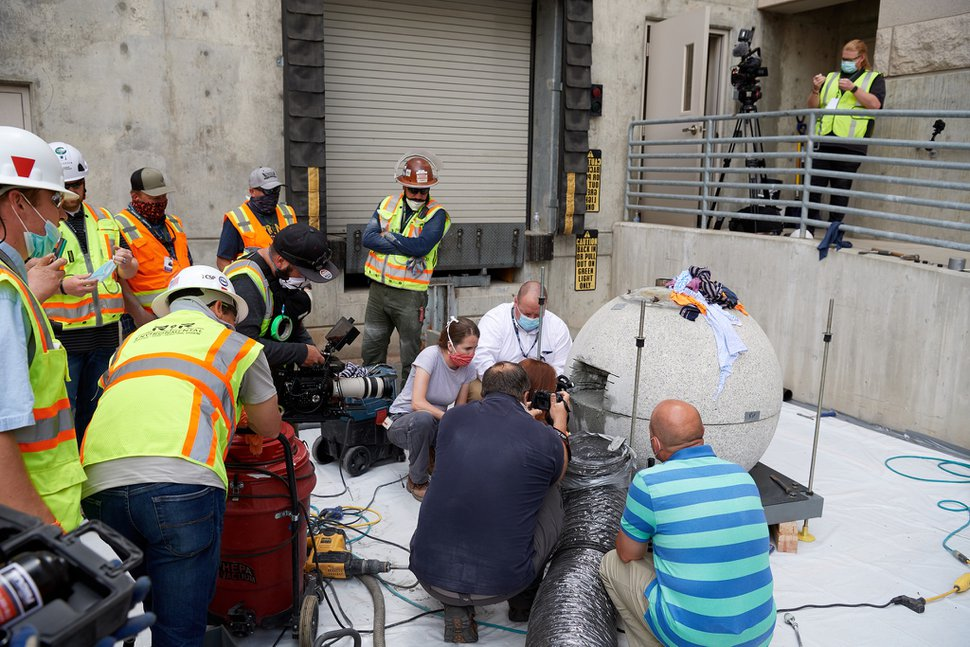 (Photo courtesy of The Church of Jesus Christ of Latter-day Saints) Preservation specialists begin the process of cutting into and retrieving items from the time capsule within the capstone of the Salt Lake Temple on May 18, 2020, at the Church History Library.