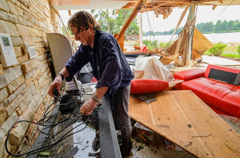 (Matthew Hinton | AP Photo) Eric Ehlenberger, a physician and neon artist, goes through his damaged home in New Orleans on Wednesday, July 10, 2019, following a storm that swamped the city and paralyzed traffic. Ehlenberger said his wife was able to crawl out safely.