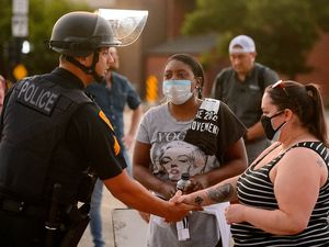 (Trent Nelson  |  Tribune file photo) A Salt Lake City police officer shakes hands with protesters marching for Black Lives Matter in this June 2, 2020, file photo. A racial equity commission is recommending changes in policing and wants feedback from residents. A virtual public hearing is scheduled for Jan. 20.