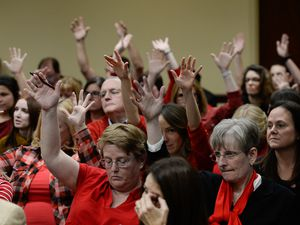 (Francisco Kjolseth  |  The Salt Lake Tribune)  Teachers in red with buttons that read #red for ed, wave their hands in support of comments made for education at the tax reform task force has what may be its final meeting at the Utah Capitol on Monday, Nov. 25, 2019, with teachers turning out in large numbers to oppose any weakening of guarantee for public education funding. A new study shows Utahns rank third in the nation in participation at public meetings.