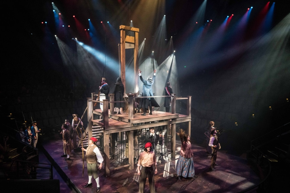 (photo courtesy Hale Centre Theatre) A guillotine and prison set descended from the ceiling for a scene from Hale Centre Theatre's 2018 production of The Scarlet Pimpernel in the company's in-the-round Centre Stage.