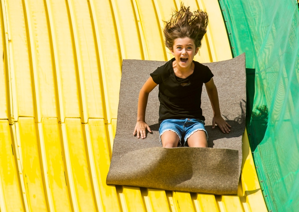 (Rick Egan | The Salt Lake Tribune) Tayah Richens 7, from Lapoint, Utah, goes down the Big Yellow Slide at the Utah State Fair, Sunday, Sept. 8, 2019.
