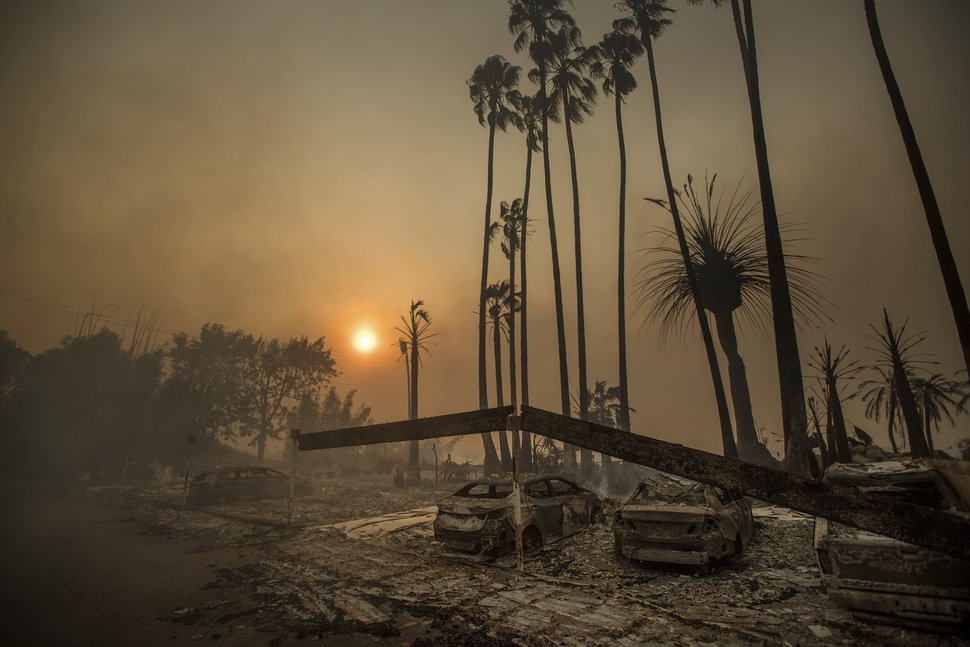 FILE - In this Dec. 5, 2017 file photo, smoke rises behind a destroyed apartment complex as a wildfire burns in Ventura, Calif. In the 30 years since 1988, the number of acres burned in the U.S. by wildfires has doubled. (AP Photo/Noah Berger, File)