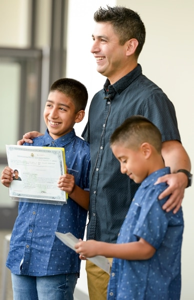 Leah Hogsten | The Salt Lake Tribune Robert Parker celebrates with his sons Sebastian Muro, 10, and Mathis Muro, 8, as American citizens after the boys' naturalization ceremony at the Viridian Event Center in West Jordan, Monday, August 6, 2018.