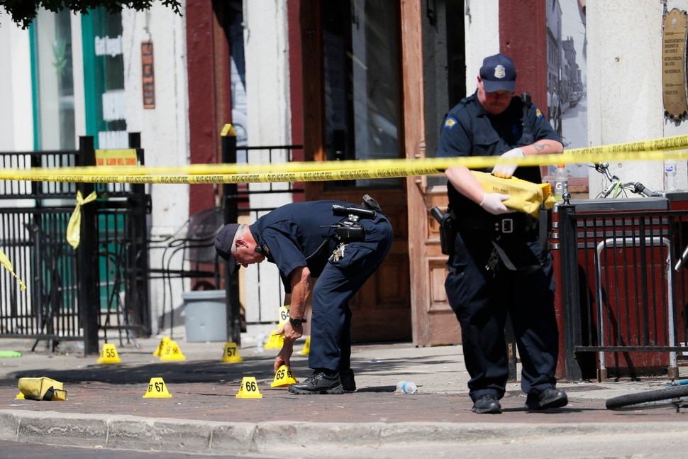 (John Minchillo |AP) Authorities retrieve evidence markers at the scene of a mass shooting, Sunday, Aug. 4, 2019, in Dayton, Ohio. Multiple people in Ohio have been killed in the second mass shooting in the U.S. in less than 24 hours, and the suspected shooter is also deceased, police said.