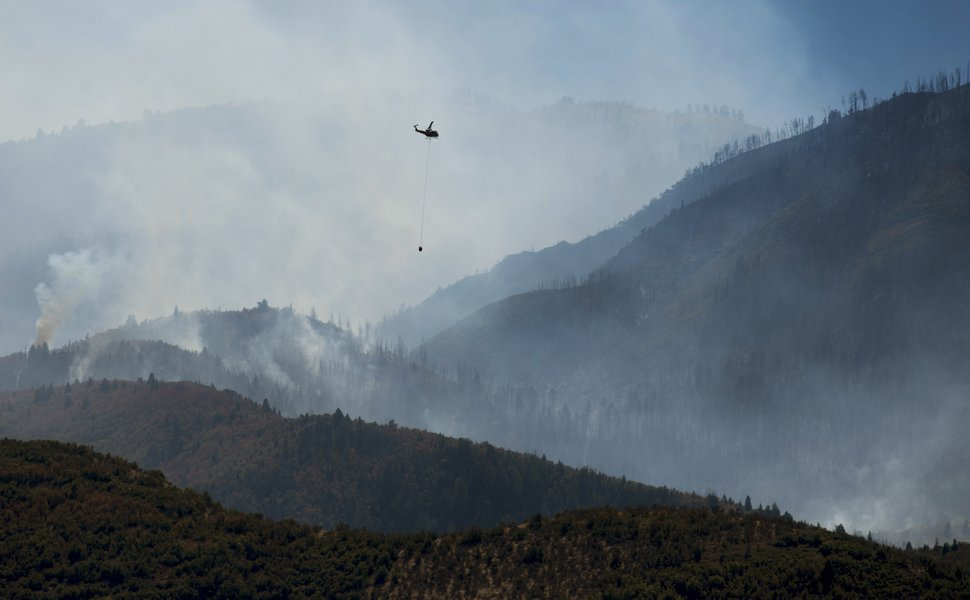 (Rick Egan | Tribune file photo) A helicopter flies over the Pole Creek Fire near Elk Ridge on Tuesday, Sept. 18, 2018.