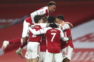 Arsenal players celebrate after Arsenal's Pierre-Emerick Aubameyang, right, scored his side's opening goal during the English Premier League soccer match between Arsenal and Leeds United at the Emirates stadium in London, England, Sunday, Feb. 14, 2021. (Catherine Ivill/Pool via AP)