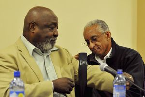 """(File photo by Andy Carpenean/Laramie Boomerang) John Griffen, right, ties a black armband on the arm of his former teammate Mel Hamilton before a """"Black 14"""" panel discussion in 2009 in Laramie, Wyo."""