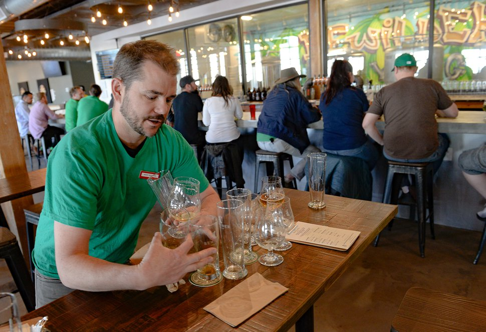 (Francisco Kjolseth | The Salt Lake Tribune) Cody McKendrick, co-owner of Bewilder Brewing Co. in Salt Lake City who says business has been down 50%, clears tables on Saturday, March 14, 2020, on a day that would have been much busier had the St. Patrick's Day parade not been cancelled. The restaurant industry has been affected by social distancing and coronavirus concerns.