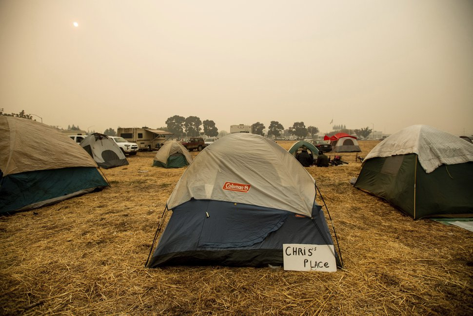 (Noah Berger | AP Photo) A sign hangs beside a tent at a makeshift shelter for evacuees of the Camp Fire in Chico, Calif., on Wednesday, Nov. 14, 2018.