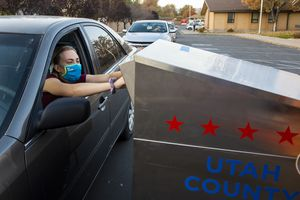 (Rick Egan | The Salt Lake Tribune) A voter drops off her ballot at the drop-off location in Lehi, on Tuesday, Nov. 3, 2020.
