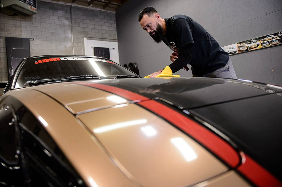 (Trent Nelson | The Salt Lake Tribune) Mauricio Rosales with a 1984 Mazda RX-7 at the Salt Lake City-based shop JDM Legends, Thursday, May 3, 2018.