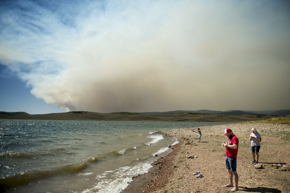 (Jeremy Harmon | The Salt Lake Tribune) Spencer Hall tries to fix a reel while fishing with his wife, Katie, and son Jonas at Strawberry Reservoir on Saturday, Sept. 15, 2018. Behind them the sky was filled with smoke from the Pole Creek Fire.