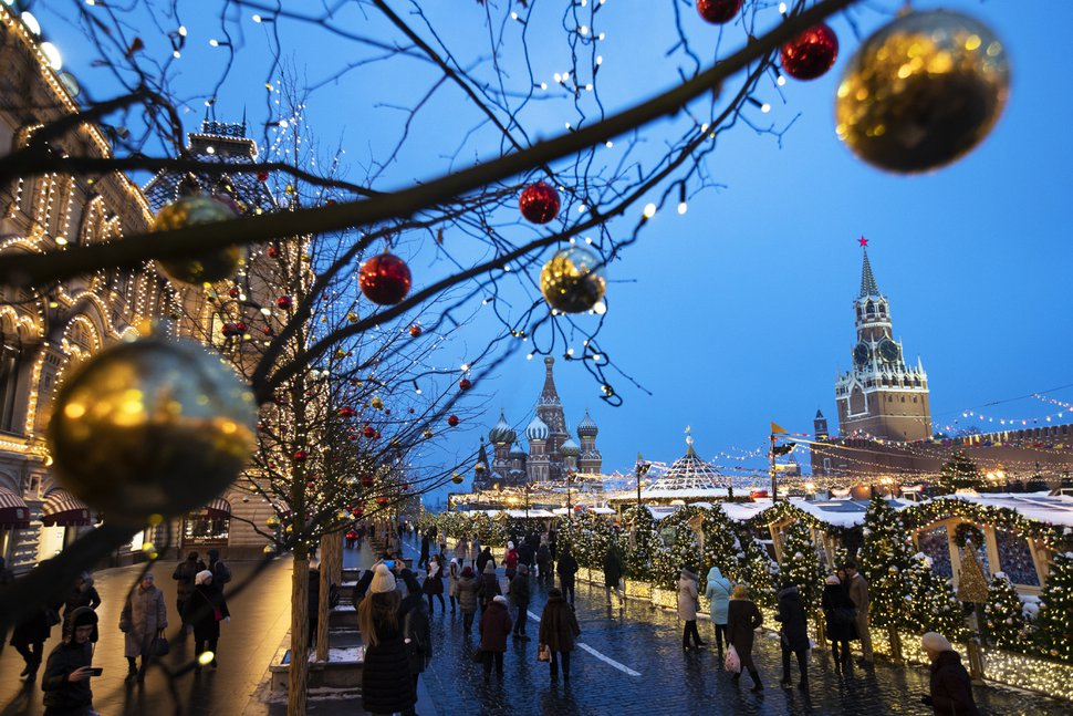 (AP Photo/Pavel Golovkin) People walk in Red Square decorated for Christmas and New Year celebrations, with the St. Basil's Cathedral, center, and the Kremlin's Spasskaya Tower, right, in the background, in Moscow, Friday, Dec. 21, 2018.