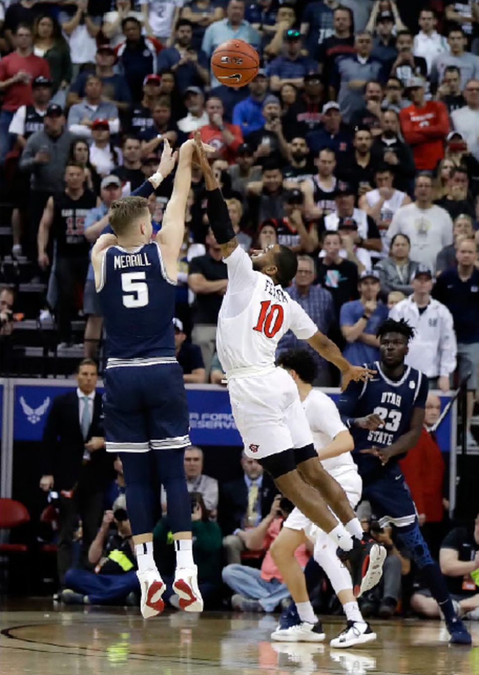Utah State's Sam Merrill (5) sinks a 3-point shot as San Diego State's KJ Feagin defends during final seconds of an NCAA college basketball game for the Mountain West Conference men's tournament championship Saturday, March 7, 2020, in Las Vegas. (AP Photo/Isaac Brekken)
