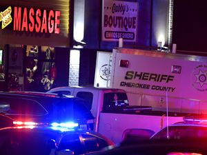 (Mike Stewart | AP) Authorities investigate a fatal shooting at a massage parlor, late Tuesday, March 16, 2021, in Acworth, Ga. Officials say 21-year-old Robert Aaron Long, of Woodstock, Georgia, has been captured hours after multiple people were killed in shootings at three Atlanta-area massage parlors.