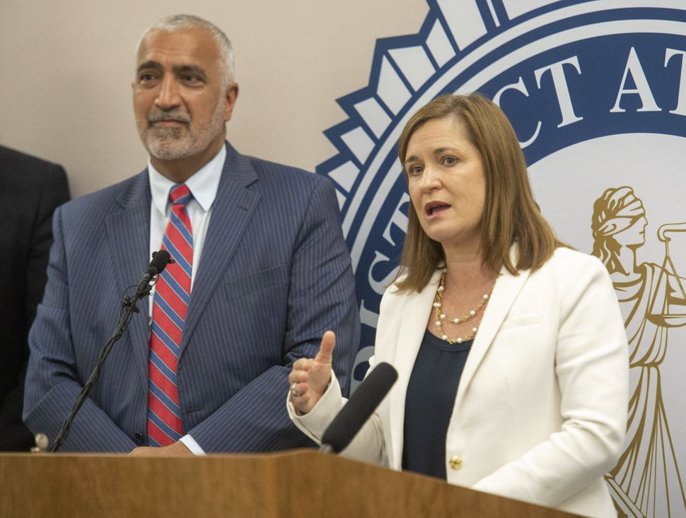 In this Tuesday, July 30, 2019, photo, Salt Lake County District Attorney Sim Gill listens as Salt Lake County Mayor Jenny Wilson, right, talks about the new diversion program for low-level offenders, during a news conference at the Salt Lake County District Attorney's Building, in Salt Lake City. The program intended to prevent individuals from entering the criminal justice system is scheduled to begin Aug. 5 and be phased in over the next 12 to 18 months, said Gill. (Rick Egan/The Salt Lake Tribune via AP)