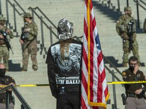 (Rick Egan | Tribune file photo) One of a dozen protesters carries an upside down flag at the Utah Capitol around noon on Sunday, Jan. 17, 2021, as beefed-up security guards the building. Lawmakers gave final approval to a bill that would expand security protection for lawmakers, their staff and even candidates who may face threats of violence.