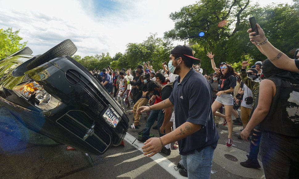 (Leah Hogsten | The Salt Lake Tribune) Protesters turn over a car belonging to Brandon McCormick and set it on fire. Hundreds marched in downtown Salt Lake City overturning two police cars and setting them on fire on Saturday, May 30, 2020, to protest the death of George Floyd.