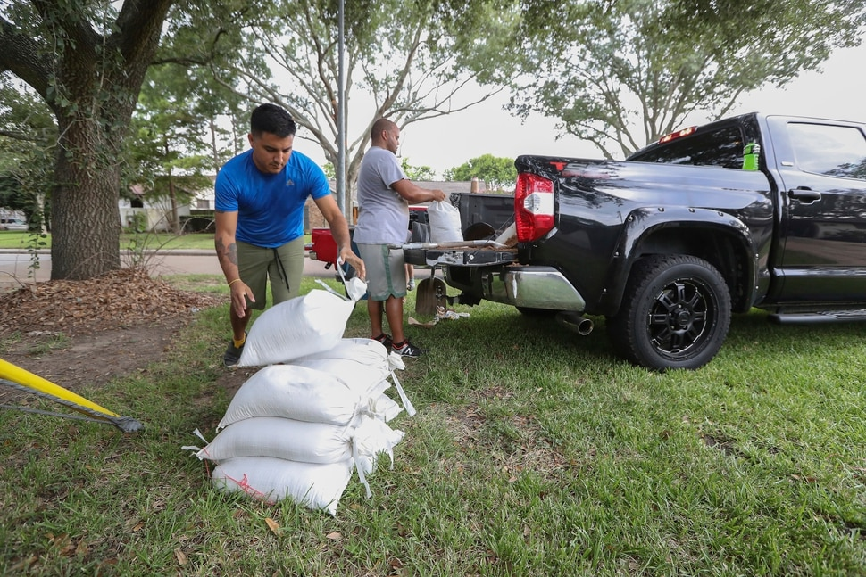 (Steve Gonzales | Houston Chronicle) Albert Martinez and Victor Valerio fill bags with dirt from a pickup Thursday, Aug. 24, 2017, in Houston. Tropical Storm Harvey intensified Thursday into a hurricane that forecasters said would be the first major hurricane to hit Texas in 12 years.