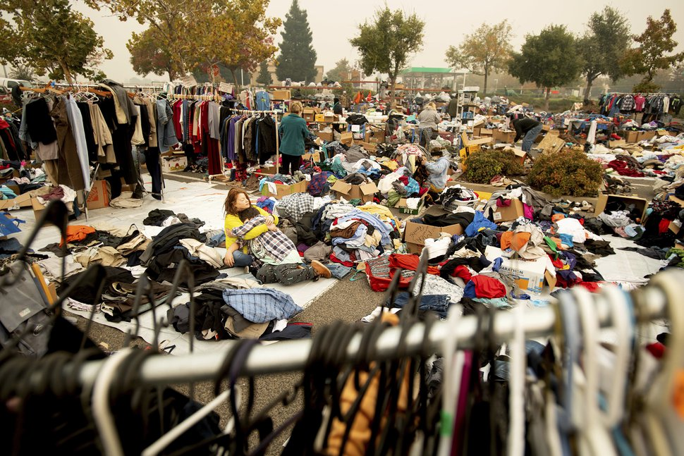 (Noah Berger | AP Photo) Denise Chester, an evacuee of the Camp Fire, hugs her son Antonio Batres as she volunteers sorting clothes at a makeshift shelter in Chico, Calif., on Wednesday, Nov. 14, 2018. Chester, who doesn't want to know yet whether her home survived, said