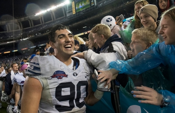 Rick Egan | The Salt Lake Tribune Brigham Young Cougars offensive lineman Corbin Kaufusi (90) celebrates with fans, after BYU defeated Wyoming 24-21in the Poinsettia Bowl, at Qualcomm Stadium in San Diego, December 21, 2016.