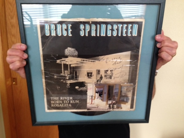 In this 2017 photo, a member of the DiGrazia family holds up a signed copy of the single Bruce Springsteen signed and mailed to Eugene DiGrazia. In 1977, Springsteen stopped at DiGrazia's Valmy Auto Court and posed for the photograph that's on the album cover. Courtesy DiGrazia family.