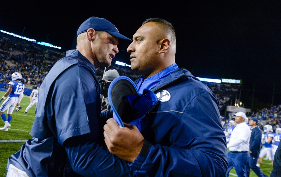 Leah Hogsten | The Salt Lake Tribune Utah State Aggies head coach Matt Wells and Brigham Young Cougars head coach Kalani Sitake shake hands after the game. Utah State University defeated BYU, 45-20, at Lavell Edwards Stadium in Provo, Friday, Oct. 5, 2018.
