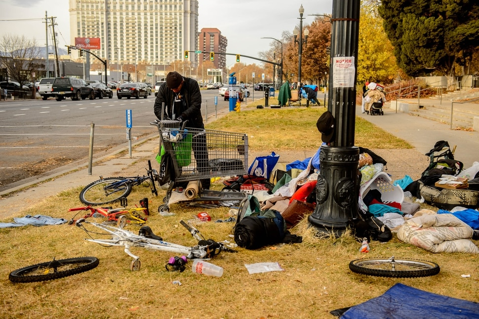 (Trent Nelson | The Salt Lake Tribune) A man empties his belongings from a shopping cart that is being reclaimed near the Salt Lake City Library on Tuesday, Nov. 19, 2019. Antonio Hernandez, an employee of Romac, is assigned to drive around the city and pick up stolen or abandoned shopping carts for return to stores.