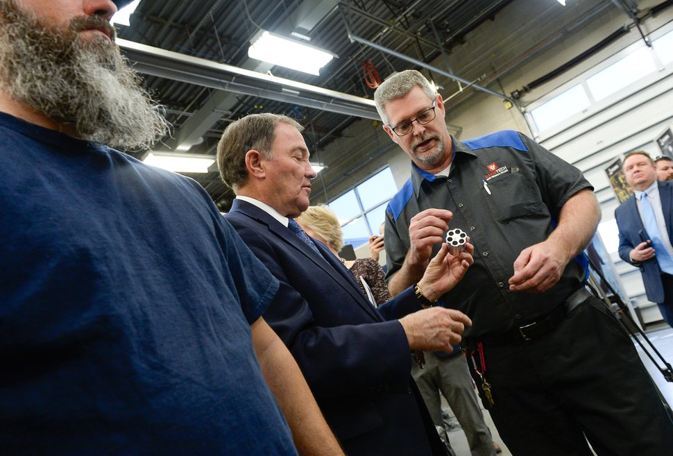(Francisco Kjolseth | The Salt Lake Tribune) Troy Winchester, right, demonstrates the capabilities of a sophisticated mill turn center machine to Gov. Gary Herbert after manufacturing a pen holder in the shape of a gun part during a visit to the Davis Technical College in Kaysville on Wed. Dec. 13, 2017. Gov. Herbert was announcing his 2018 budget proposal.