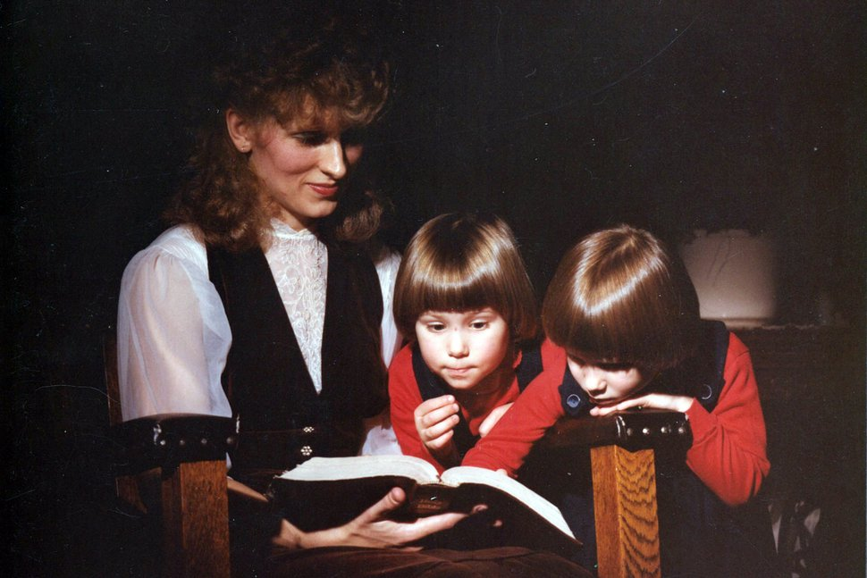 (Coral Theill via AP) This image provided by Coral Theill, shows Theill with her twin boys in 1984, reading from their family Bible.
