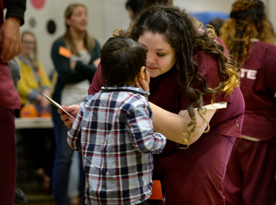 (Scott Sommerdorf | The Salt Lake Tribune) Elicia Chavez cradles her son Damiano's face in her hand as they visit in the prison gymnasium during