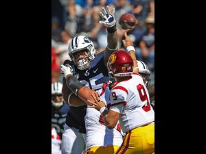 (George Frey | AP Photo) BYU defensive lineman Khyiris Tonga (95) tries to knock down a pass from Southern California quarterback Kedon Slovis (9) in the first half of an NCAA college football game, Saturday, Sept. 14, 2019, in Provo, Utah. BYU defeated USC 30-27.