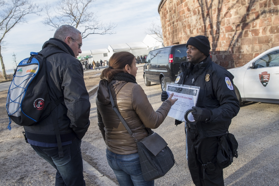 United States Park Police officer Fernandez, right, inform tourist that the Statue of Liberty is closed, Saturday, Jan. 20, 2018, in New York. The National Park Service announced that the Statue of Liberty and Ellis Island would be closed Saturday due to a lapse in appropriations. Late Friday, the Senate failed to approve legislation to keep the government from shutting down after the midnight deadline. (AP Photo/Mary Altaffer)