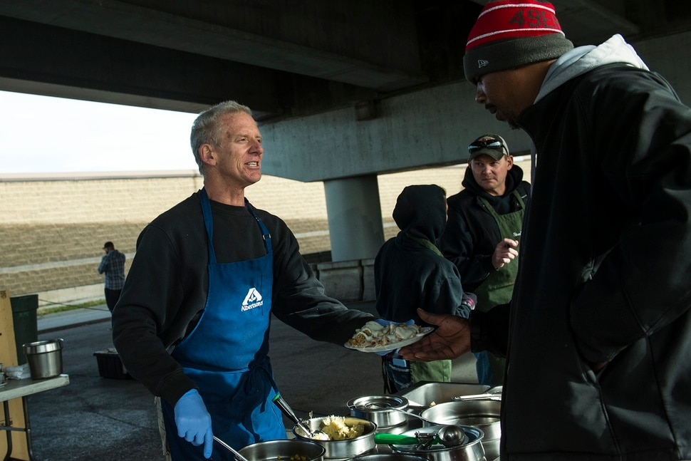 (Chris Detrick   The Salt Lake Tribune) Volunteer Brent Levetan serves a Thanksgiving Day meal to Jason Hall during the Eagle Ranch Chuckwagon under the viaduct at 500 South and 600 West in Salt Lake City Thursday, November 23, 2017.