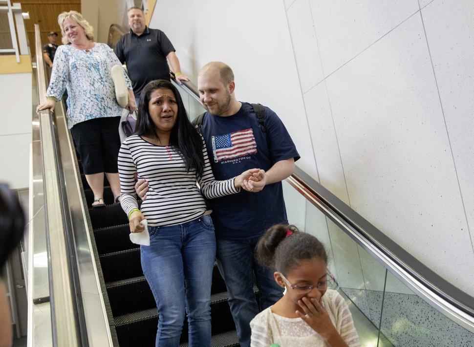 Thamara Caleno, left, Josh, right, and Marian Holt, bottom, react to a crowd of friends, family and supporters upon returning to Salt Lake City after receiving medical care and visiting President Donald Trump in Washington on Monday, May 28, 2018. Holt was freed this weekend after being held in a Venezuelan jail for nearly two years. (AP Photo/Kim Raff)