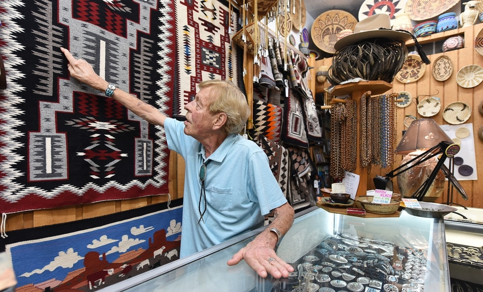 (Francisco Kjolseth | The Salt Lake Tribune) Dave Dunn, owner of TP Gallery, an institution on Main Street for over 44 years, talks about the intricate work on an authentic Native American tapestry as he welcomes patrons to his store on Wed. Aug. 21, 2019. The store is scheduled to close sometime before the end of the year.
