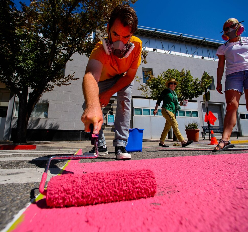 (Trent Nelson | The Salt Lake Tribune) Tyler Bloomquist works on Jann Haworth's Rose art project on Broadway in Salt Lake City on Sunday Aug. 11, 2019. From left, Bloomquist, Haworth, and Lauren Brown.