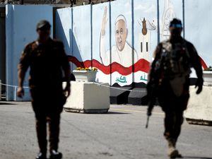 Federal policemen patrol by a concrete wall placed by Iraqi security forces to surround the Our Lady of Salvation Church during preparations for the Pope's visit in Mar Youssif Church in Baghdad, Iraq, Friday, Feb. 26, 2021. (AP/Photo/Hadi Mizban)