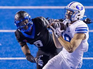 BYU wide receiver Gunner Romney secures a pass from quarterback Zach Wilson (1) defended by Boise State cornerback Markel Reed (8) Friday, Nov. 6, 2020, at the Albertsons Stadium in Boise, Idaho. (Darin Oswald/Idaho Statesman via AP)