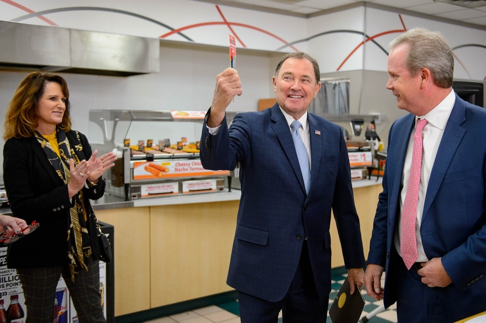 """(Trent Nelson   The Salt Lake Tribune) Utah Gov. Gary Herbert holds up his new Speedy Rewards card, given to him by Speedway President Timothy Griffith at the opening of a new Speedway convenience store and gas station that will sell lower-sulfur """"Tier 3"""" gasoline, in Salt Lake City on Monday Nov. 25, 2019. At left is Speedway's VP of Corporate Affairs Karma Thomson."""