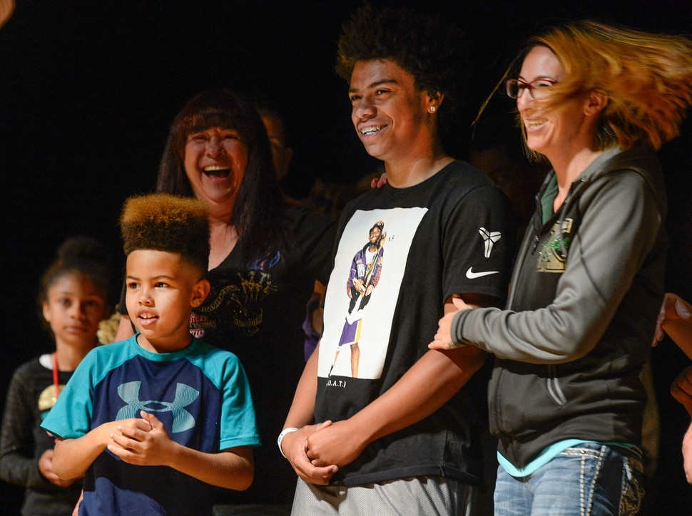 (Francisco Kjolseth | The Salt Lake Tribune) Kearns High sophomore Keeven Wilson, 16, is announced as the Granite School District's Absolutely Incredible Kid award winner alongside his brother Kamani, 9, and foster mother Jessica Wilson during the school farewell assembly on Tuesday, May 22, 2018. Wilson who had a particularly difficult home life, to the point that he and his siblings were taken away from his parents along with near universal F's during his junior high days, turned his life around. With the help of a new foster family, teachers and his football coach, he is now an honor roll student and thinking of studying psychology in college.